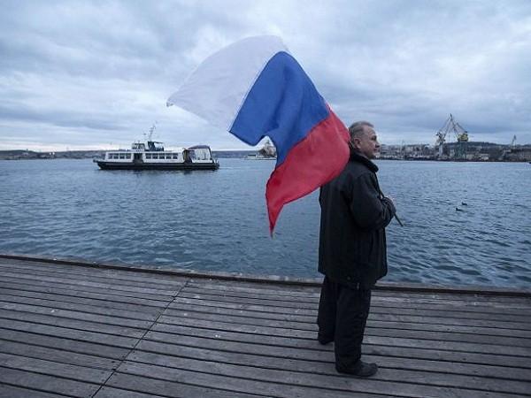Một người Nga vẫy cờ ở cảng Sevastopol của Crimea