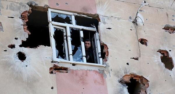 Một người đàn ông đứng trong tòa nhà bị tàn phá sau cuộc tấn công của quân đội chính phủ vào thành phố Diyarbakir