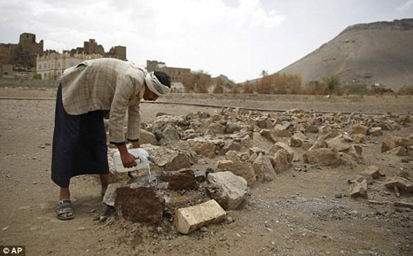 Cha của Udai đang tưới nước lên nấm mộ của cậu bé, nằm không xa từ ngôi làng nghèo khó