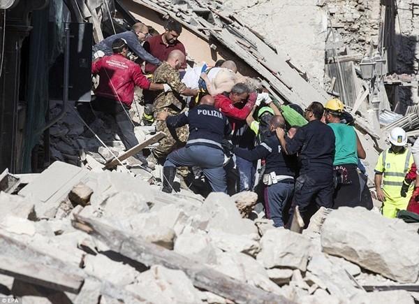 Lực lượng cứu hộ vận chuyển một nạn nhân vừa cứu được khỏi ngôi nhà của ông