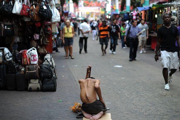 Một người ăn xin què quặt ngồi xin tiền trên đường phố Malaysia
