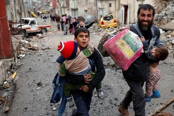Một gia đình bồng bế nhau cố gắng chạy trốn khỏi Mosul, nơi đang diễn ra cuộc giao tranh ác liệt của quân đội chính phủ và IS