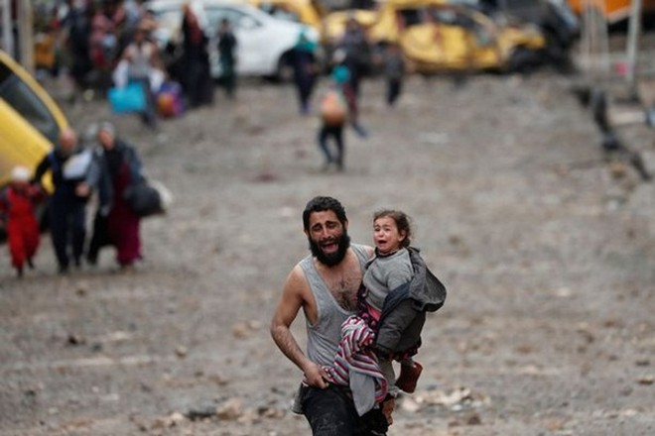 Người đàn ông này vừa ôm con gái vừa khóc khi bom đạn dội trúng vào ngôi nhà của mình, khiến các thành viên khác thiệt mạng