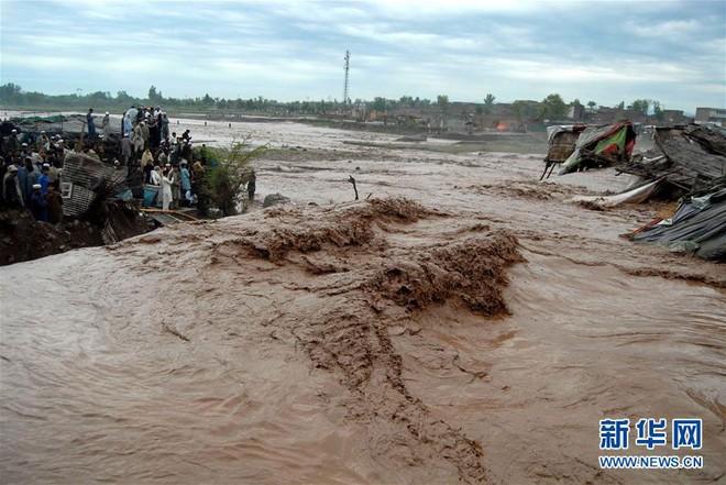 Người dân Pakistan đứng trên mô đất cao khi lũ lụt tràn qua khu chợ ở ngoại ô thành phố Peshawar