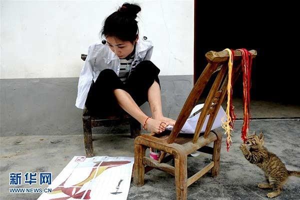 Dương Bội cần mẫn thêu tranh bằng chân