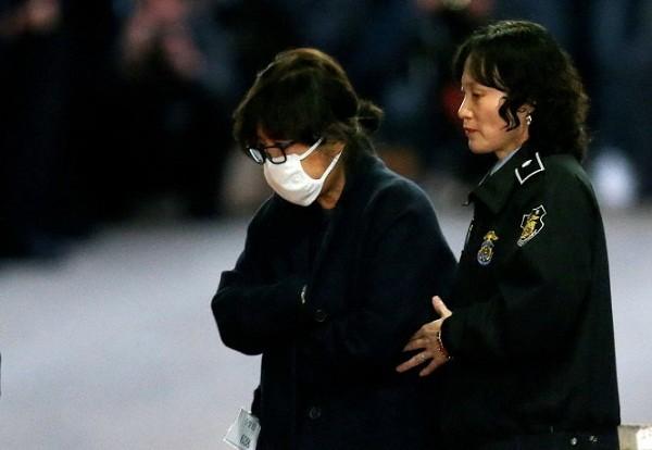 Bà Choi Soon-sil (đeo khẩu trang) rời tòa án ở Seoul sau khi nghe đọc lệnh bắt giữ