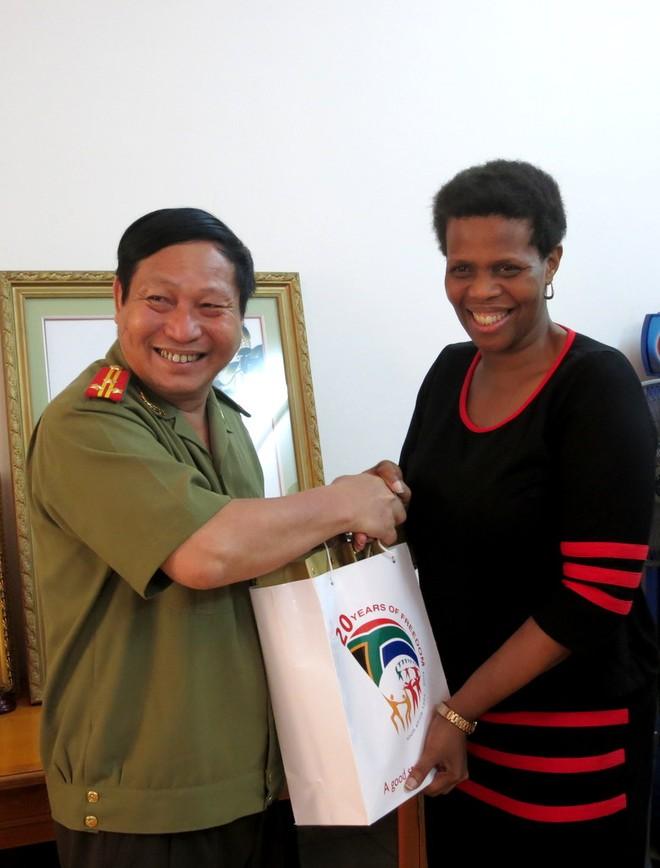 Đại sứ Nam Phi Kgomotso Ruth Magau vui mừng trao quà và chụp ảnh lưu niệm với Thượng tá An Văn Huân, Phó Tổng biên tập báo An ninh Thủ đô