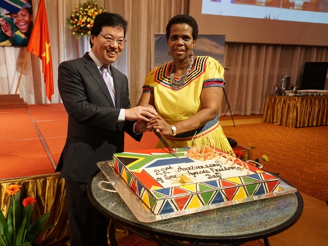 Ông Dương Chí Dũng, Trợ lý Bộ trưởng, Chánh Văn phòng Bộ Ngoại giao Việt Nam và bà Kgomotso Ruth Magau, Đại sứ đặc mệnh toàn quyền Cộng hòa Nam Phi tại Việt Nam cắt chiếc bánh kỷ niệm 22 năm Ngày Nam Phi tự do.