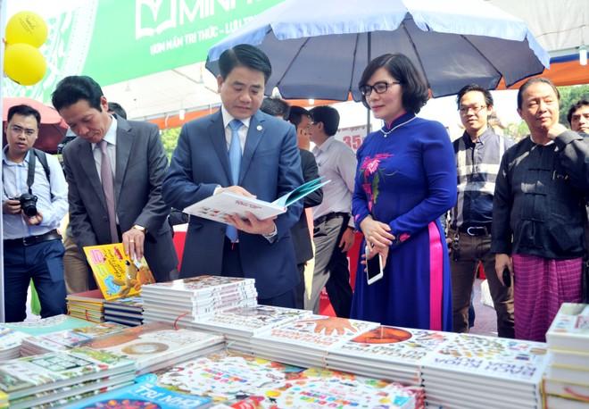 Chủ tịch UBND Thành phố Hà Nội Nguyễn Đức Chung và Giám đốc Sở TT-TT Phan Lan Tú tham quan một gian hàng sách