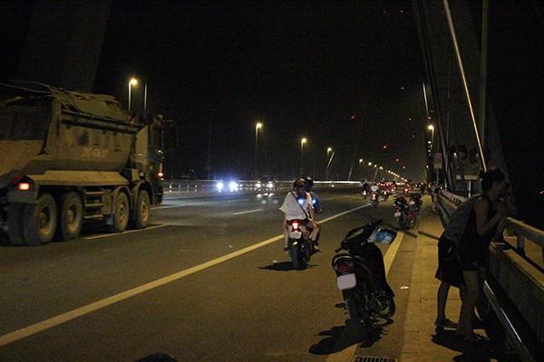 Xe máy dừng, đỗ tràn lan trên cầu Nhật Tân khiến nhiều phương tiện khác phải lưu thông sang làn xe ô tô.