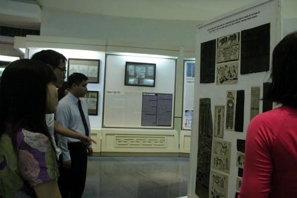Hướng dẫn viên giới thiệu cho mọi người những dòng tranh tại buổi triển lãm.