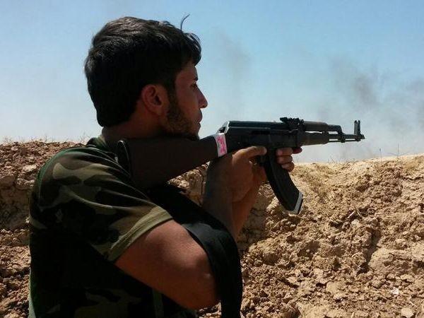 Một tay súng chống IS đang nã đạn về phía kẻ thù