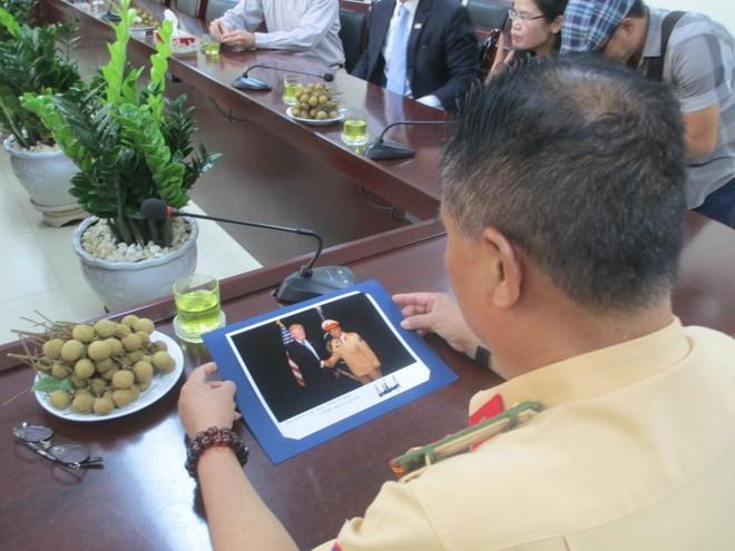 Đại tá Đào Vịnh Thắng xem bức hình ghi lại kỷ niệm trong chuyến công du Việt Nam của Tổng thống Mỹ Donald Trump