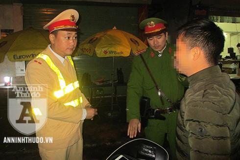 Thượng úy Hoàng Minh Trường (ngoài cùng, bên trái) giải thích cho người vi phạm