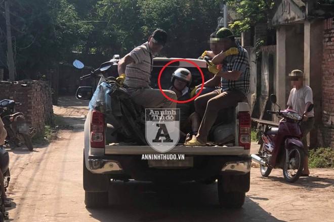 Các trinh sát Hình sự Đặc nhiệm bắt giữ Đỗ Văn Bình (khoanh đỏ), áp giải về bằng xe ô tô bán tải
