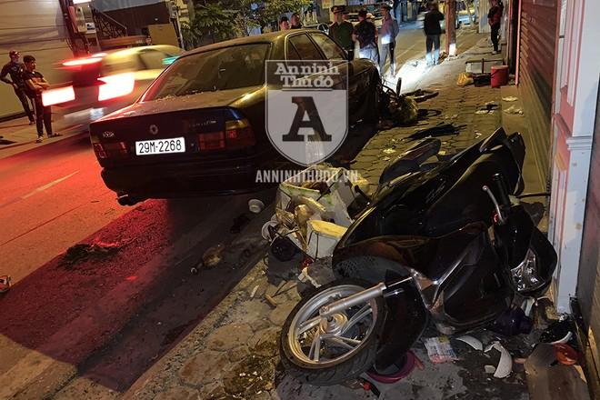"""Trong khi xe máy dừng ở vỉa hè bị đâm đổ, thì xe máy đỗ sát mép đường bị """"ngoạm"""" một phần vào gầm xe"""