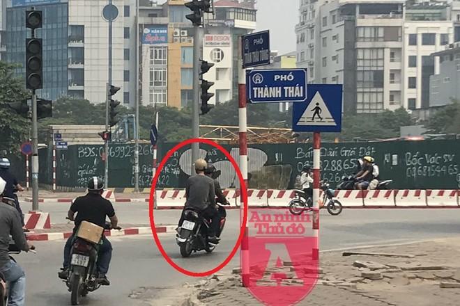 """Đây là hình ảnh đặc biệt chưa từng được công bố. Hai đối tượng đèo nhau trên xe máy (khoanh đỏ) là Phương - Phú. Chúng đang trong quá trình """"săn mồi"""" mà không hề biết trinh sát hình sự luôn bám sát. Tay của Phú để trên đùi và luôn cầm sẵn dao bấm"""