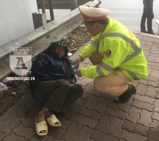 Đại úy Hoàng Minh Trường hỏi thăm để nắm tình hình của người đàn ông nằm ở gầm cầu trong thời tiết mưa lạnh