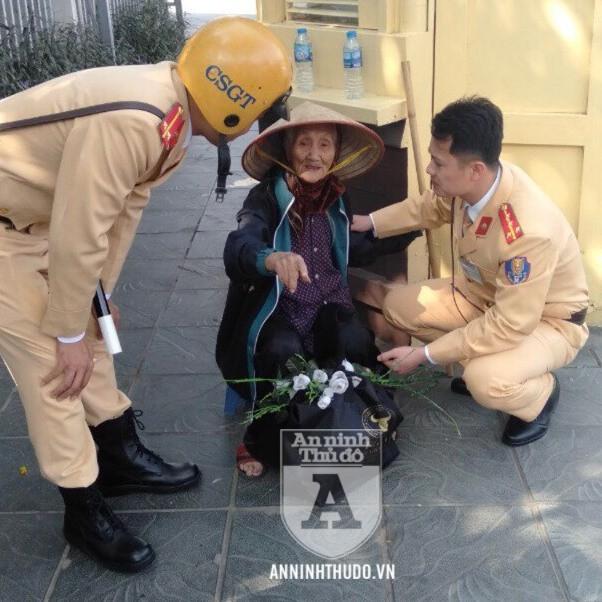 Bà cụ cao tuổi được cán bộ CSGT đưa vào chỗ tránh nắng, hỏi thăm và mời uống nước