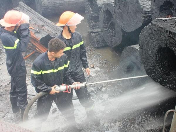 Khoảng 30 phút sau, ngọn lửa được khống chế nhưng các chiến sỹ PCCC vẫn phải xịt nước vào những khúc gỗ đang cháy âm ỉ