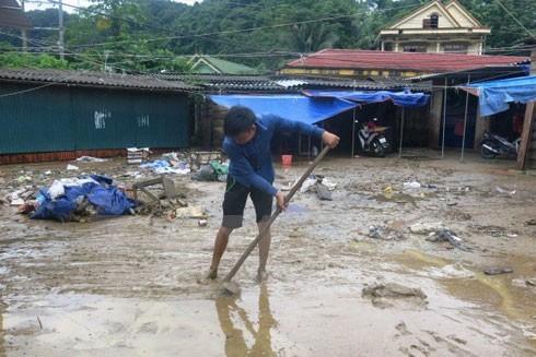 Người dân huyện Minh Hóa đang dọn dẹp nhà, cửa hàng sau khi nước rút