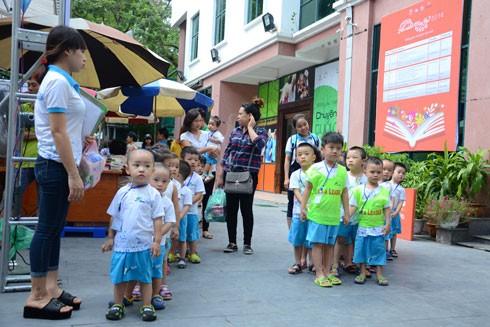 Các em bé học mẫu giáo đang xếp hàng để vào tham quan hội sách