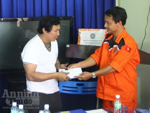 Ông Nguyễn Xuân Bình (bên phải), Phó giám đốc Nha Trang MRCC trao tiền hỗ trợ cho thuyền trường tàu cá QNa 95959TS