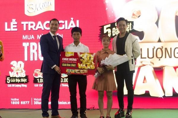 Nghệ sĩ Trấn Thành cùng ông Nguyễn Thế Anh (bìa trái) – Phó Tổng Giám đốc Công ty CP UNIBEN trao giải thưởng 30 lượng vàng đầu tiên cho gia đình anh Đặng Văn Mười (Quảng Nam)