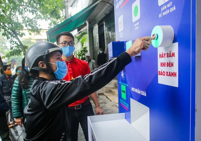 Người lao động xếp hàng để nhận lương thực từ cây ATM gạo