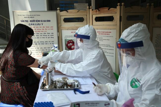 Nhân viên y tế lấy mẫu xét nghiệm Covid-19 với người dân trở về từ Đà Nẵng