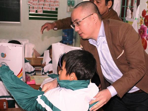 Ông Nguyễn Phan Huy Khôi, Giám đốc Đối ngoại, Tập đoàn Number 1 (Tân Hiệp Phát) mặc áo ấm cho một em nhỏ dân tộc Vân Kiều tại trường Tiểu học Trường Sơn, huyện Quảng Ninh.
