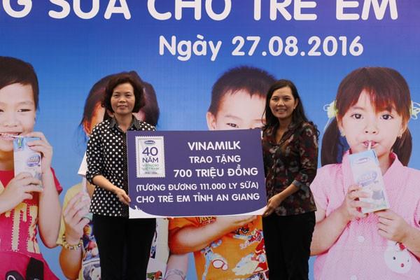 Bà Bùi Thị Hương - Giám đốc điều hành Vinamilk trao tặng bảng tượng trưng 700 triệu đồng, tương đương 111.000 ly sữa của Quỹ Sữa vươn cao Việt Nam cho trẻ em nghèo An Giang.