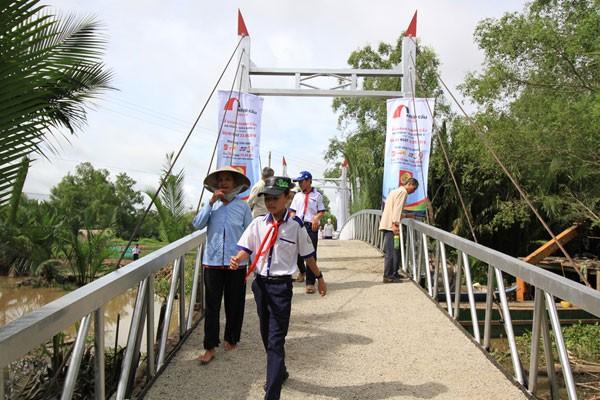Những người dân, em học sinh vui mừng đi trên cây cầu thép dây văng vừa khánh thành.