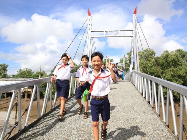 Những em học sinh của trường tiểu học Hiệp Vinh vui mừng đi trên cây cầu mới