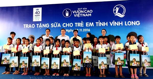 Các đại biểu trao tặng sữa cho các em học sinh trường tiểu học Hoà Bình A, xã Hoà Bình, huyện Trà Ôn, tỉnh Vĩnh Long, trong chương trình Quỹ sữa vươn cao Việt Nam tại Vĩnh Long.
