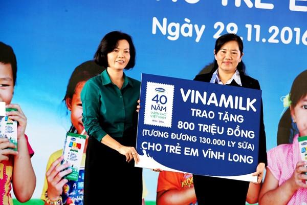 Bà Bùi Thị Hương – Giám đốc điều hành Vinamilk trao tặng bảng tượng trưng 130.000 ly sữa với tổng trị giá 800 triệu đồng của Quỹ sữa vươn cao Việt Nam cho học sinh nghèo Vĩnh Long