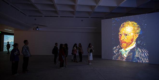 """""""Bản thân triển lãm này có thể xem là một tác phẩm nghệ thuật. Các bức tranh không còn ở tỷ lệ 1:1 mà hiển thị dưới dạng hình ảnh số, được phóng lên những bức tường rất lớn trong một không gian rộng mở và tối giản - tạo thành một sắp đặt giàu tính đương đại"""","""