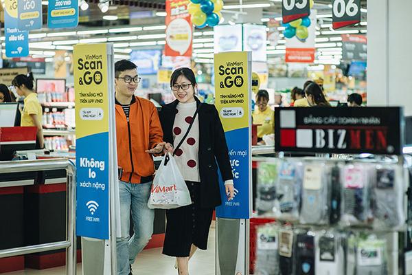 """Một đôi vợ chồng trẻ vui vẻ xách túi hàng ra về sau khi """"thanh toán siêu tốc"""" bằng VinMart Scan &Go"""