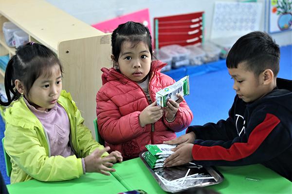 Các con tham gia chương trình Sữa học đường Hà Nội tự uống và tự gấp gọn gàng vỏ hộp sữa sau khi uống xong cho vào thùng rác