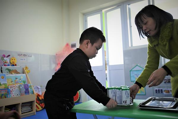 Cô giáo chuẩn bị sữa cho các bé tham gia chương trình Sữa học đường tại một điểm trường ở Hà Nội.
