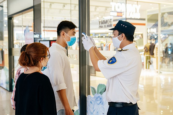 Nhân viên an ninh đo thân nhiệt toàn bộ khách ra/vào TTTM để giảm thiểu nguy cơ lây nhiễm chéo