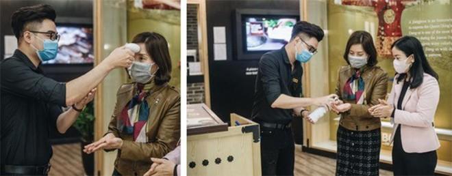 Khách hàng được rửa tay sát trùng và đo nhiệt độ trước khi vào một nhà hàng ở Hà Nội