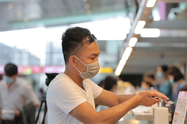 Hành khách rửa tay bằng nước sát khuẩn tại sân bay Vân Đồn