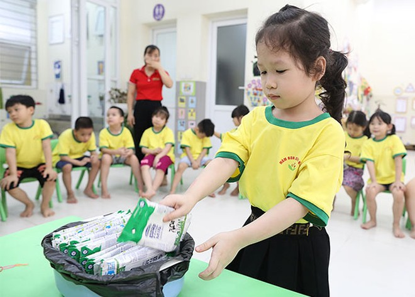 Các em học sinh được hướng dẫn cách gấp gọn và thu dọn hộp sữa sau khi sử dụng xong