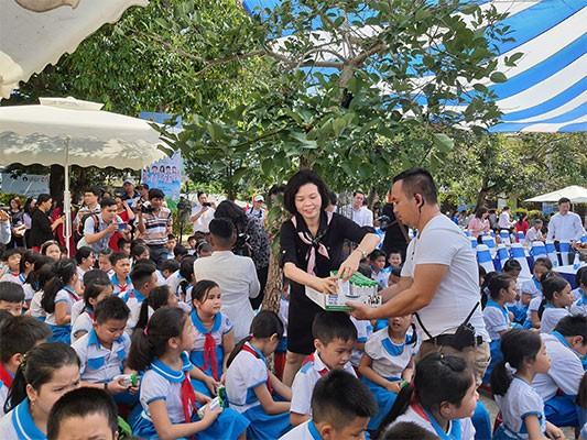 Các em học sinh trường Kim Đồng hồ hởi đón nhận những hộp sữa đầu tiên trong chương trình Sữa học đường từ bà Bùi Thị Hương – Giám đốc điều hành Vinamilk