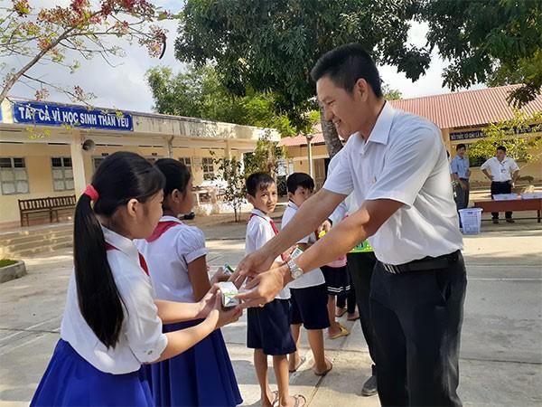Các thầy cô giáo phát sữa cho các em học sinh nhân ngày đầu tiên bắt đầu uống sữa học đường