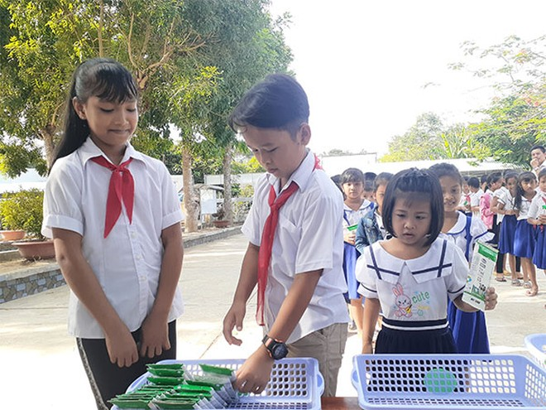 Các em học sinh thực hành gấp vỏ hộp sữa sau khi uống để dễ thu gom và tái chế