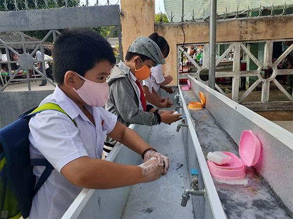 Học sinh được hướng dẫn đeo khẩu trang ở nơi đông người và rửa tay trước khi vào lớp học