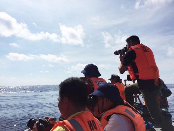 Phóng viên Báo An ninh Thủ đô (đứng) tác nghiệp ngay trên xuồng vào đảo giữa tròng trành sóng nước