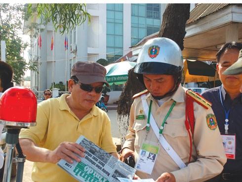 Đại tá Đào Lê Bình tặng ấn phẩm Báo ANTĐ cho Cảnh sát giao thông Lào